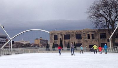Skaters make their way across ice lightly covered with snow at Brenton Skating Plaza in downtown Des Moines, Iowa, on Dec. 6, 2012. (Associated Press