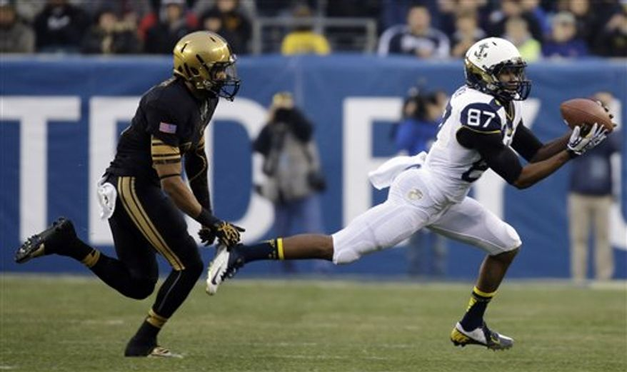 Navy's Shawn Lynch, right, pulls in a pass as Army's Josh Jackson chases during the first half of an NCAA college football game, Saturday, Dec. 8, 2012, in Philadelphia. (AP Photo/Matt Slocum)