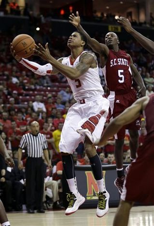 Maryland guard Nick Faust shoots past South Carolina State guard Adama Adams, of Senegal, in the second half of an NCAA college basketball game in College Park, Md., Saturday, Dec. 8, 2012. Maryland won 61-46. (AP Photo/Patrick Semansky)