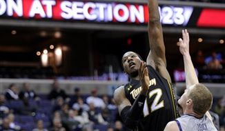 Towson forward Barrington Alston (12) shoots over Georgetown forward Nate Lubick (34) during the first half of an NCAA college basketball game, Saturday, Dec. 8, 2012, in Washington. (AP Photo/Nick Wass)