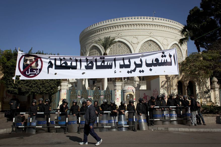 """An Egyptian passes riot policemen guarding a gate of the presidential palace under a banner with a defaced picture of president Mohammed Morsi and Arabic that reads """"the people want to bring down the regime,"""" at the protests site, in Cairo, Egypt, Saturday, Dec. 8, 2012. Egypt's military has warned of 'disastrous consequences' if the political crisis gripping the country is not resolved through dialogue. (AP Photo/Nasser Nasser)"""