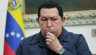 ** FILE ** Venezuelan President Hugo Chavez kisses a crucifix before a surgery in Cuba to treat cancer in December 2012. (Associated Press)