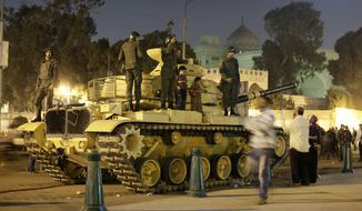 An Egyptian protester takes a picture with his mobile phone of his children on top of an Egyptian army tank outside the presidential palace (background) in Cairo on Saturday, Dec. 8, 2012. (AP Photo/Hassan Ammar)
