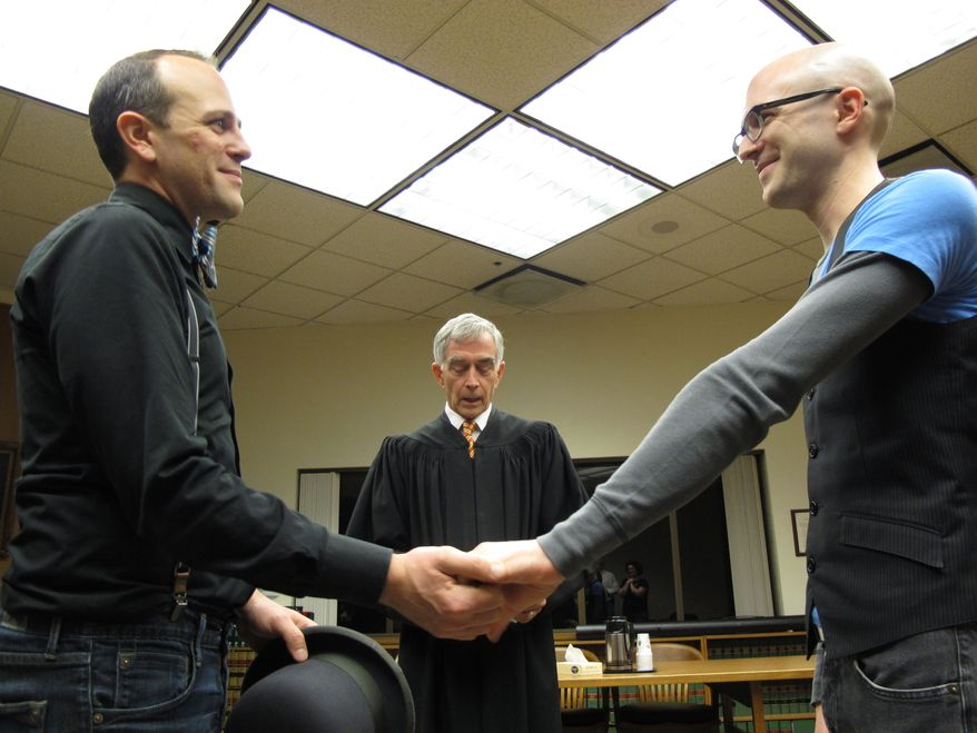Matthew Wiltse (right) and Jonathon Bashford (left) are married by Thurston County Superior Court Judge Chris Wickham at the Thurston County Courthouse just after midnight on Sunday, Dec. 9, 2012, in Olympia, Wash. Sunday is the first day that same-sex couples can marry under Washington state's new voter-approved law allowing gay marriage. (AP Photo/Rachel La Corte)