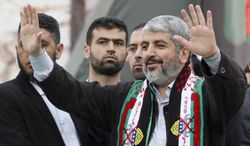 Hamas chief Khaled Mashaal waves to Palestinian Hamas supporters during a rally to commemorate the 25th anniversary of the militant group, in Gaza City, Gaza Strip, on Saturday, Dec. 8, 2012. (AP Photo/Hatem Moussa)