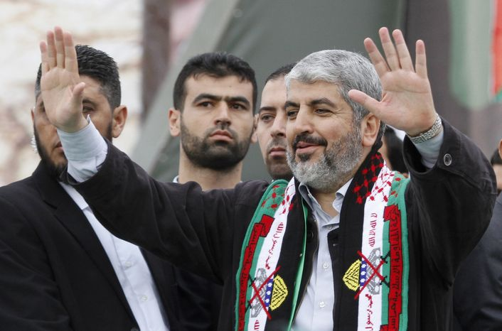 Hamas chief Khaled Mashaal waves to Palestinian Hamas supporters during a rally to commemorate the 25th anniversary of the militant group, in Gaza City, Gaza Strip, on Saturday, Dec