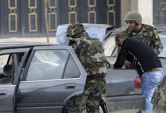 ** FILE ** Lebanese soldiers search a car at a checkpoint after they were deployed to calm clashes that erupted between pro- and anti-Syrian-regime gunmen in the northern port city of Tripoli, Lebanon, on Wednesday, Dec. 5, 2012. (AP Photo/Hussein Malla)