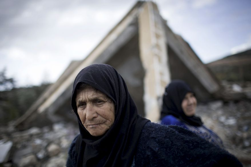 Syrian women stand amid the ruins of their farm, destroyed by government army jets, in the village of Al-Hafriyeh, Syria, on Saturday, Dec. 8, 2012. (AP Photo/Manu Brabo)