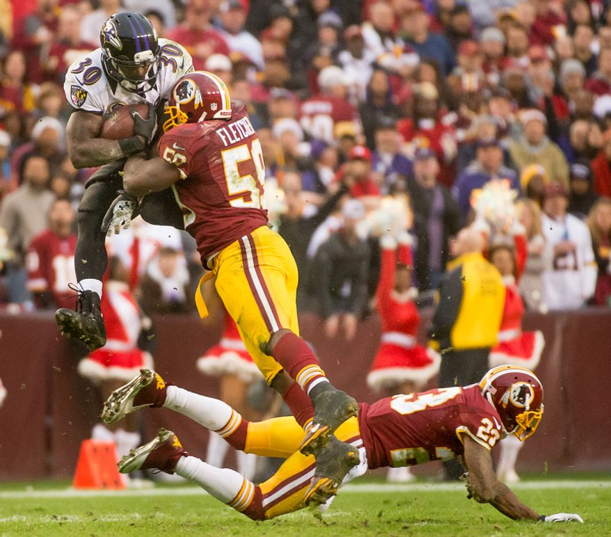 Baltimore Ravens running back Bernard Pierce (30) is tackled by Washington Redskins inside linebacker London Fletcher (59) as he jumps over Washington Redskins cornerback DeAngelo Hall (23) on an 11 yard pass play in the fouth quarter as the Washington Redskins play the Baltimore Ravens at Fedex Field, Landover, Md., Sunday, December 9, 2012. (Andrew Harnik/The Washington Times)