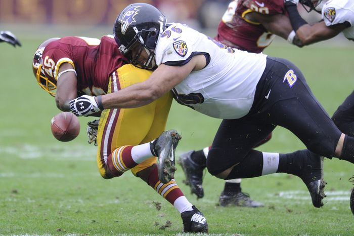 Baltimore Ravens nose tackle Ma'ake Kemoeatu (96) forces Washington Redskins running back Alfred Morris (46) to fumble in the second quarter at FedEx Field, Landover, M