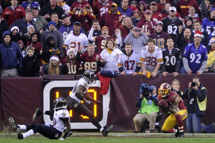 Washington Redskins wide receiver Pierre Garcon (88) hauls in an 11-yard touchdown pass in front of Baltimore Ravens free safety Ed Reed (20) and defensive back Chris Johnson (39) in the final minute of regulation at FedEx Field, Landover, Md