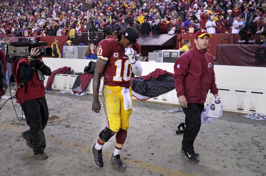 Washington Redskins quarterback Robert Griffin III (10) leaves the field with a brace on his injured right leg after defeating the Ravens 31-28 at FedEx Field, Landover, Md., Dec. 9, 2012. (Preston Keres/Special to The Washington Times)