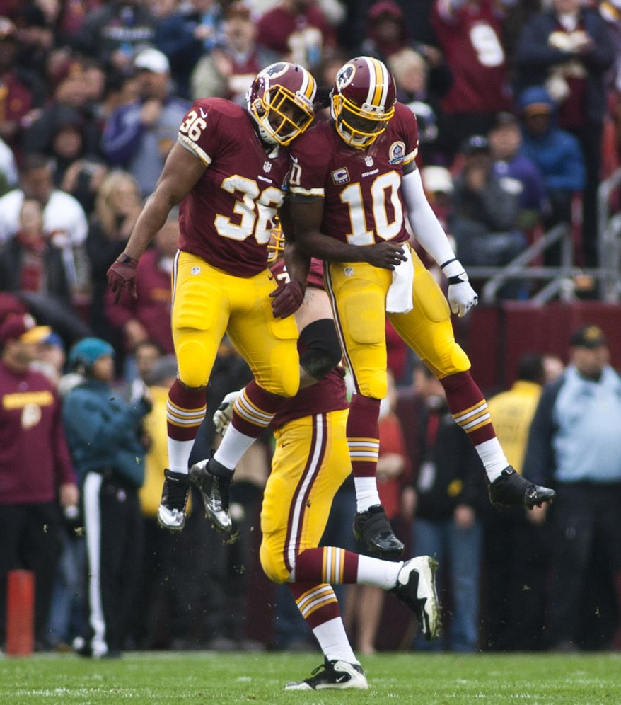 Washington Redskins quarterback Robert Griffin III (10) celebrates with fullback Darrel Young (36) after scoring a touchdown in the first half against the Baltimore Ravens at FedEx Field in Landover Md., on Sunday, December 9, 2012. (Craig Bisacre/The Washington Times)