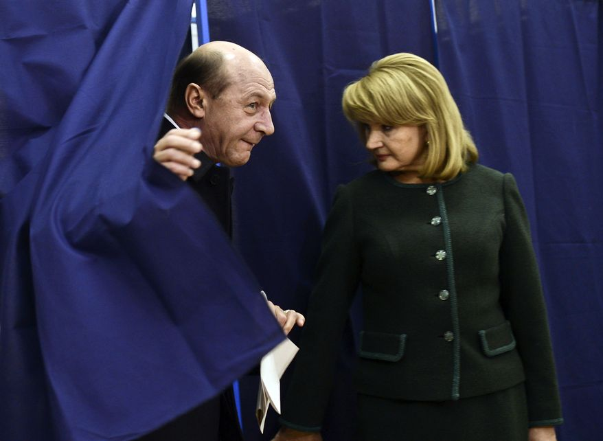 Romanian President Traian Basescu (left) exits a voting booth as his wife, Maria, stands by in Bucharest, Romania, on Sunday, Dec. 9, 2012. Millions of Romanians braved rain and snow as they went to the polls for a parliamentary election that center-left government is expected to win, but the result could lead to more of the political instability that has plagued the impoverished Balkan nation this year. (AP Photo)