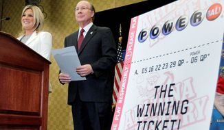 Arizona Lottery Director of Budget, Products and Communications Karen Bach (left) and Executive Director Jeff Hatch-Miller displayed an enlargement of the winning $587.5 million Powerball ticket at a news conference Friday in Scottsdale. Two people with the winning numbers have come forward. (Associated Press)