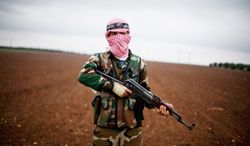 A Free Syrian Army fighter takes position close to a military base north of Aleppo on Monday. The gains by rebel forces came as the European Union denounced the Syrian conflict, which activists say has killed more than 40,000 people. (Associated Press)