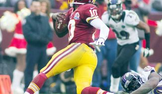 Playing with abandon is what makes Robert Griffin III the player he is, even if it means the potential for absorbing hard hits, such as this one by Baltimore tackle Haloti Ngata (left) during the Redskins' 31-28 overtime win Sunday. (Craig Bisacre/The Washington Times)