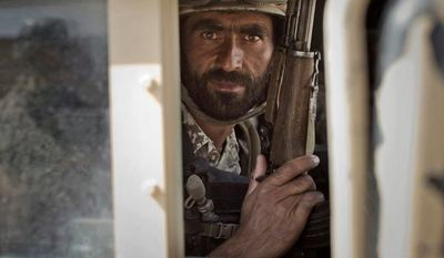 In this Friday, Oct. 19, 2012 photo, a member of Afghanistan's elite Civil Order Police looks through a window of his armored vehicle during a patrol in Marjah, southern Helmand province, Afghanistan.  (AP Photo/Anja Niedringhaus)