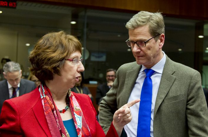 European Union foreign policy chief Catherine Ashton (left) speaks with German Foreign Minister Guido Westerwelle during a meeting of EU foreign ministers at the EU Council building in Brussels on Monday, Dec. 10, 2012. (AP Photo/Virginia Mayo)