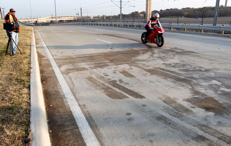 A news cameraman films the aftermath as a motorcyclist drives by the site of a single-vehicle accident involving Dallas Cowboys player Josh Brent on Dec. 8, 2012, in Irving, Texas. Brent is facing an intoxication manslaughter charge after the accident killed teammate Jerry Brown, a linebacker on the team's practice squad. (Associated Press)