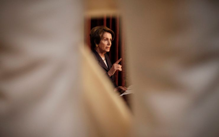 **FILE** House Minority Leader Nancy Pelosi, California Democrat, is framed through the marble statue of Lewis Cass, representing Michigan, by Daniel Chester French, as she speaks during a news conference in Statuary Hall on Capitol Hill in Washington on Dec. 7, 2012. (Associated Press)