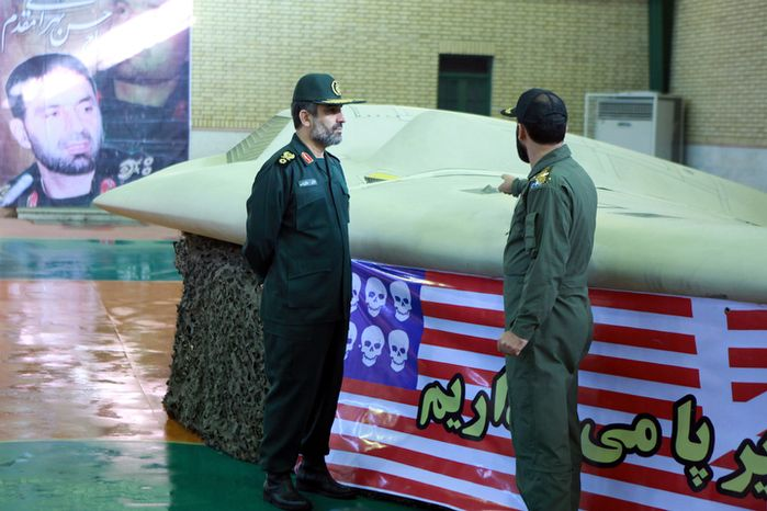 ** FILE ** This photo released Dec. 8, 2011, by the Iranian Revolutionary Guards claims to show Gen. Amir Ali Hajizadeh (left), the chief of the aerospace division of Iran's Revolutionary Guards, listening to an unidentified colonel as he points to a U.S. RQ-170 Sentinel drone that Tehran said its force