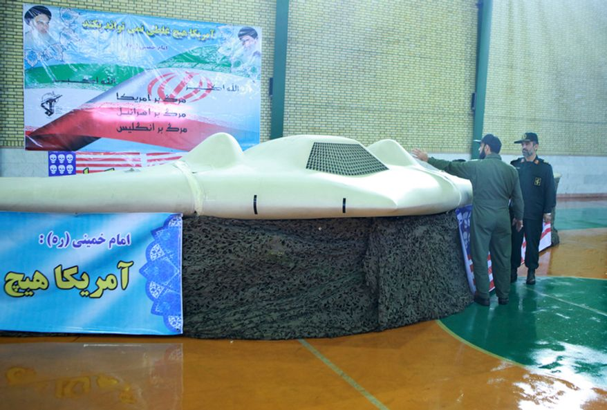 This photo released Dec. 8, 2011, by the Iranian Revolutionary Guards claims to show a U.S. RQ-170 Sentinel drone that Tehran said its forces downed earlier in the week, as Gen. Amir Ali Hajizadeh (right), chief of the aerospace division of Iran's Revolutionary Guards, listens to an unidentified colonel in an undisclosed location in Iran. (Associated Press/Sepahnews)