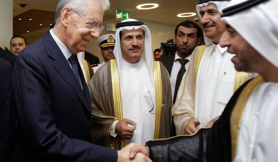 **FILE** Italian prime minister Mario Monti (left) shakes hands with a UAE official as he arrives Nov. 20, 2012, to the UAE-Italy Business Forum at the Dubai Chamber of Commerce & Industry in Dubai, United Arab Emirates, with Sultan bin Saeed al Mansoori, UAE minister of economy (second left). (Associated Press)