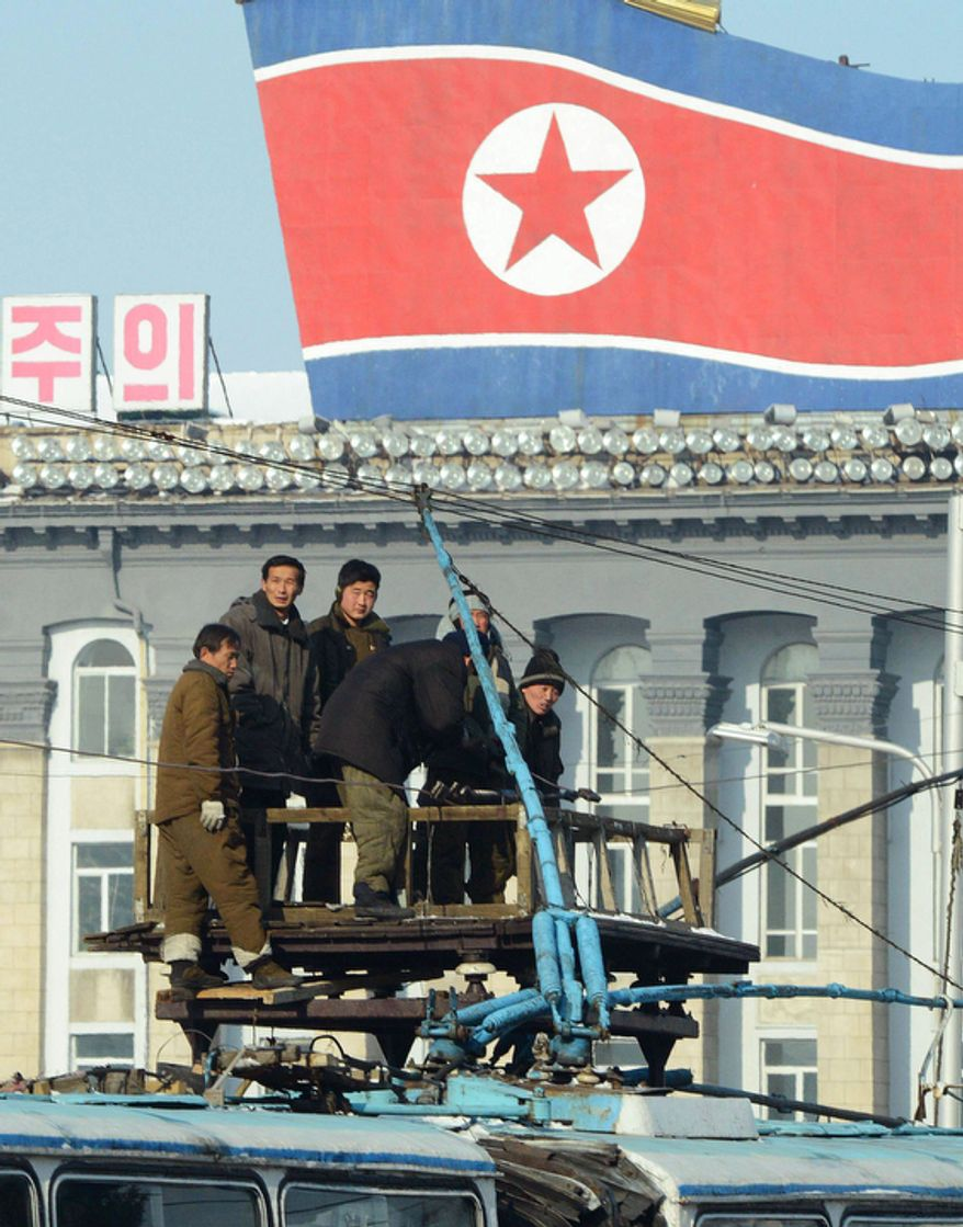 North Korean men work atop a trolleybus in Pyongyang, North Korea, on Dec. 10, 2012. North Korea extended the launch period for a controversial long-range rocket by another week until Dec. 29, citing technical problems. (Associated Press/Kyodo News)