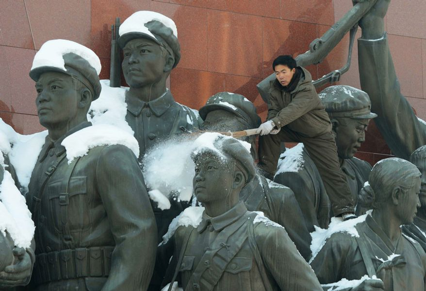 A North Korean man scrapes snow from the monument of anti-Japanese revolutionary fighters on Mansu Hill in Pyongyang, North Korea, on Dec. 10, 2012. North Korea extended the launch period for a controversial long-range rocket by another week until Dec. 29, citing technical problems. (Associated Press/Kyodo News)