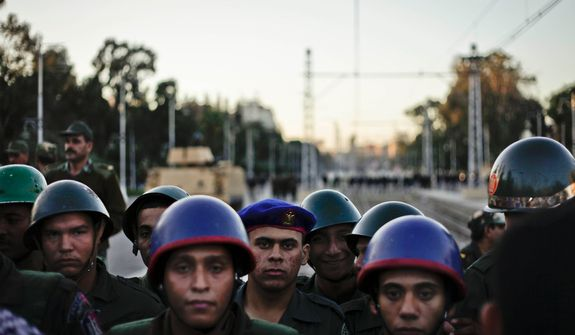 Egyptian army soldiers stand guard during a demonstration in front of the presidential palace in Cairo on Dec. 7, 2012. (Associated Press)