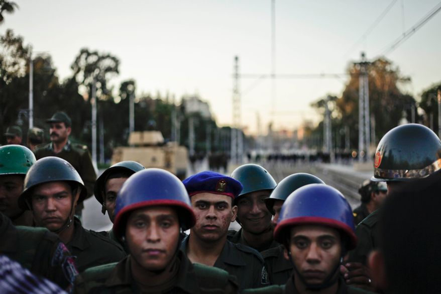 Egyptian army soldiers stand guard during a demonstration in front of the presidential palace in Cairo, Egypt, Friday, Dec. 7, 2012. (AP Photo/Nariman El-Mofty)