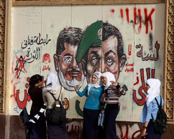 Young girls pose for a photograph by a wall painted with graffiti showing President Mohammed Morsi, left, and a split portrait of former Defense Minister, Hussain Tantawi, center, and former President Hosni Mobarak, right, in front of the Presidential Palace in Cairo, Egypt, Monday, Dec. 10, 2012. (AP Photo/Petr David Josek)