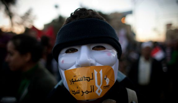 "An Egyptian protester with a mask on his face and a sticker with Arabic that reads ""No for the constitution of the Morshid"" during a protest against President Mohammed Morsi near the presidential palace in Cairo on Dec. 7, 2012. (Associated Press)"