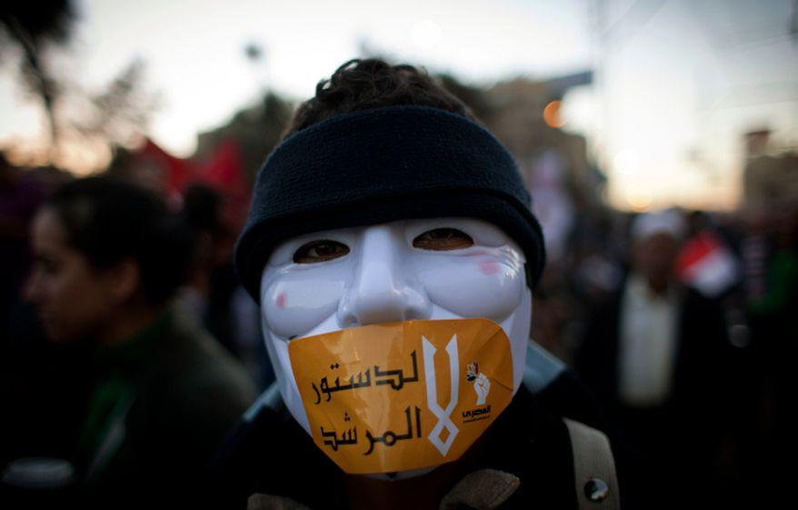 "An Egyptian protester with a mask on his face and a sticker with Arabic that reads ""No for the constitution of the Morshid,"" during an anti president Mohammed Morsi protest near the presidential palace, in Cairo, Egypt, Friday, Dec. 7, 2012. (AP Photo/Nasser Nasser)"