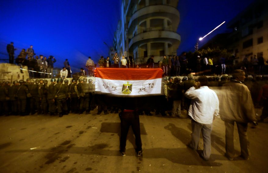 A protester holds the Egyptian national flag as army soldiers stand guard near the presidential palace in Cairo on Dec. 9, 2012. (Associated Press)