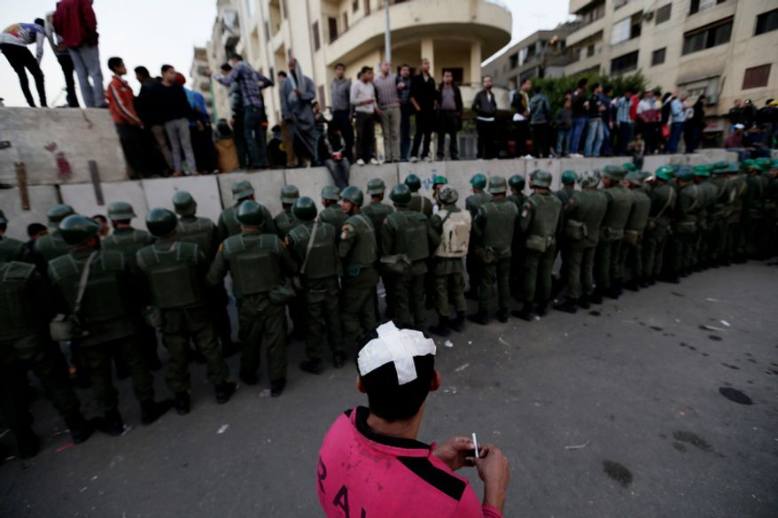 Egyptian army soldiers stand guard as protesters stand on top of cement blocks near the presidential palace in Cairo, Egypt, Sunday, Dec. 9, 2012. (AP Photo/Hassan Ammar)