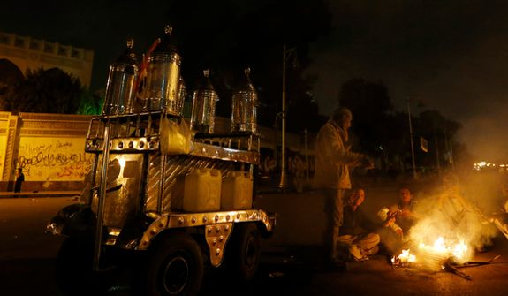 Protesters make a bonfire in front of the presidential palace (background) in Cairo on Dec. 9, 2012. Egypt's liberal opposition called for more protests, seeking to keep up the momentum of its street campaign after the president made a partial concession overnight but refused its main demand he rescind a draft constitution going to a referendum on Dec. 15. (Associated Press)