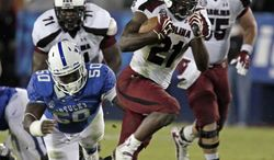 FILE - This Sept. 29, 2012, file photo shows South Carolina running back Marcus Lattimore (21) running away from Kentucky's Mike Douglas (50) during the second half of an NCAA college football game in Lexington, Ky. Lattimore will enter the NFL draft, said people familiar with the decision. One person said Monday, Dec. 10, 2012, that Lattimore is expected to announce his decision later this week. The people spoke with The Associated Press on condition of anonymity because there has not been an official statements regarding Lattimore's decision. (AP Photo/Garry Jones, File)
