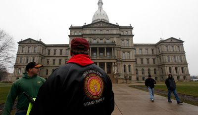 ** FILE ** International Brotherhood of Electrical Workers members stand outside the capitol in Lansing, Friday, Dec. 7, 2012. (AP Photo/Paul Sancya)