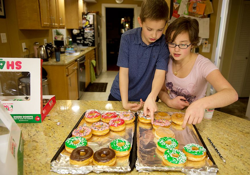 """Wil Hiday gets help from sister Chase, 15, to perfect his arrangement of donuts in the shape of the number """"12"""" on two cookie sheets in their Vienna, Va. home on Tuesday, Dec. 11, 2012. Wil, who will turn 12 Wednesday on 12/12/12, plans on bringing the donuts to school to share with friends. Tonight he and his family will celebrate at IHOP at the stroke of midnight. (Barbara L. Salisbury/The Washington Times)"""