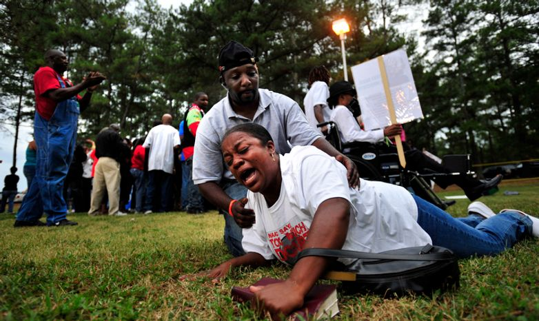**FILE** An anti-death penalty protester in Jackson, Ga., is helped off the ground Sept. 21, 2011, after hearing about a delay of the execution of Georgia death row inmate Troy Davis by the U.S. Supreme Court. Davis was convicted of kil