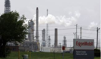 **FILE** Steam rises from towers at an Exxon Mobil refinery in Baytown, Texas, on April 16, 2010. (Associated Press)