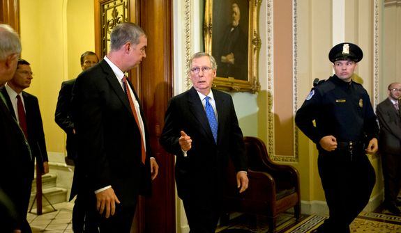 Senate Minority Leader Mitch McConnell (center), Kentucky Republican, steps off the Senate floor at the Capitol in Washington on Tuesday, Nov. 27, 2012, before speaking with reporters following a GOP strategy luncheon. (AP Photo/J. Scott Applewhite)