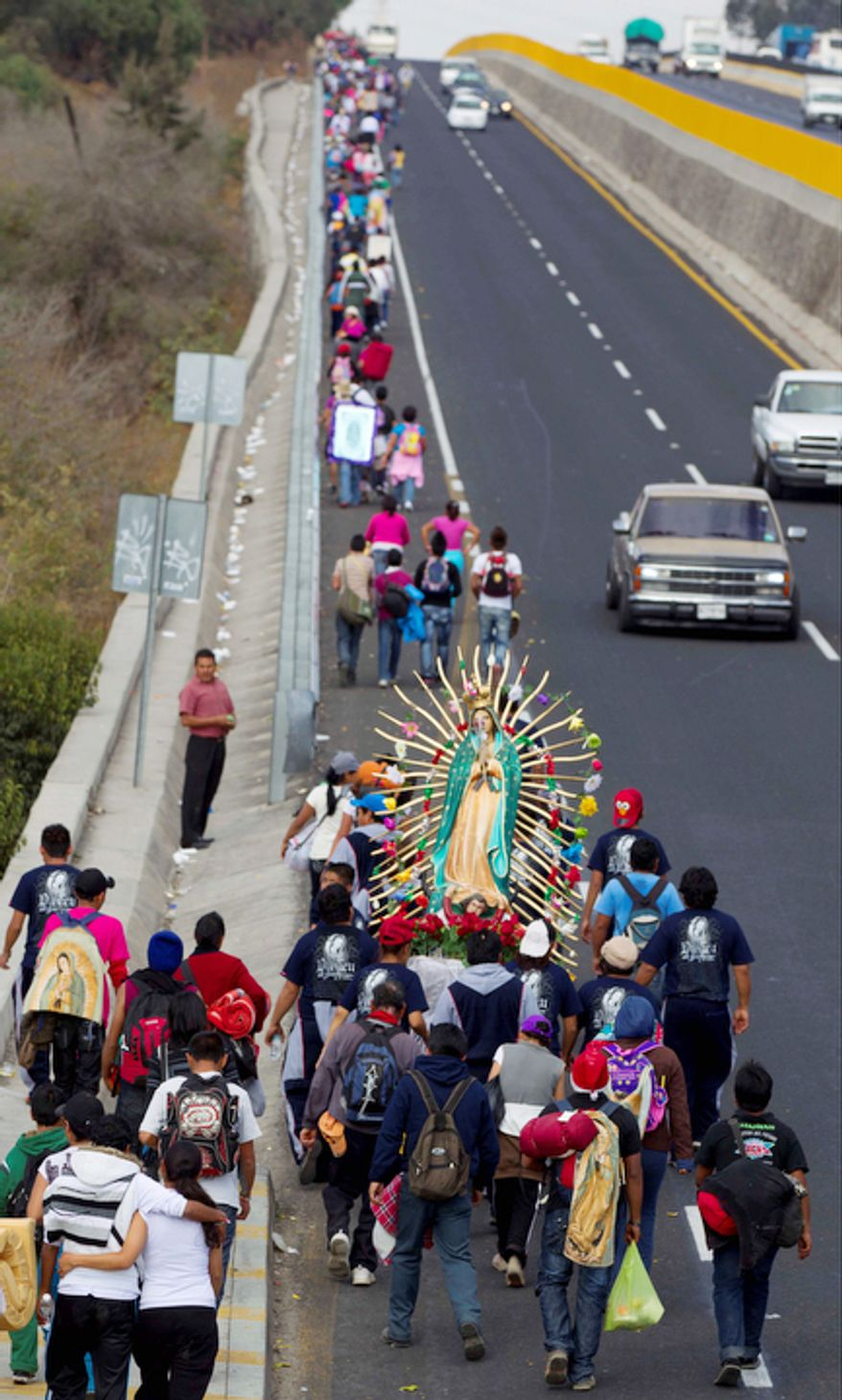Pilgrims carry a statue of the Virgin of Guadalupe as they walk along the shoulder of a highway toward the Basilica of Guadalupe at the entrance to Mexico City, Tuesday, Dec. 11. 2012.   (AP Photo/Eduardo Verdugo)