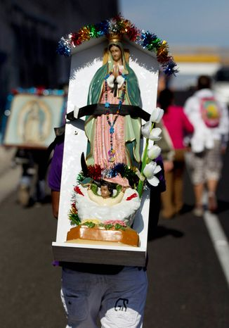 A pilgrim carries a statue of the Virgin of Guadalupe on his back as he makes his way with other pilgrims toward the Basilica of Guadalupe in Mexico. (AP Photo/Eduardo Verdugo)