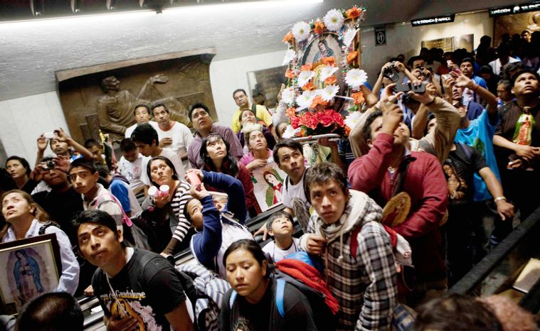 People carrying images of the Virgin of Guadalujpe look up at the original image of her inside the Basilica of Guadalupe in Mexico City, Tuesday Dec. 11, 2012.  Nationwide, devotees of the Virgin of Guadalupe make a pilgrimage to the basilica with images of her to be blessed in honor of her Dec. 12 feast day. (AP Photo/Eduardo Verdugo)