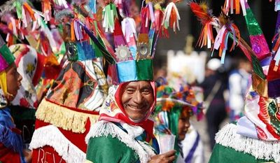 """Francisco Castillo, 62, part of a group of pilgrims from Puebla state performing the """"Danza de los Negritos"""" smiles while taking a break during the festivities of the Virgin of Guadalupe at the Basilica of Guadalupe  in Mexico City. (AP Photo/Denisse Pohls)"""