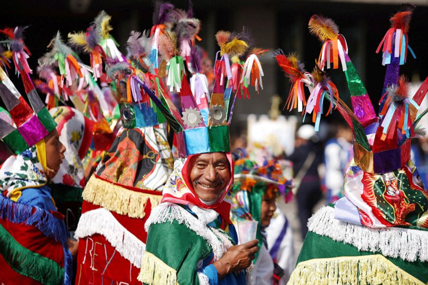 "Francisco Castillo, 62, part of a group of pilgrims from Puebla state performing the ""Danza de los Negritos"" smiles while taking a break during the festivities of the Virgin of Guadalupe at the Basilica of Guadalupe  in Mexico City. (AP Photo/Denisse Pohls)"