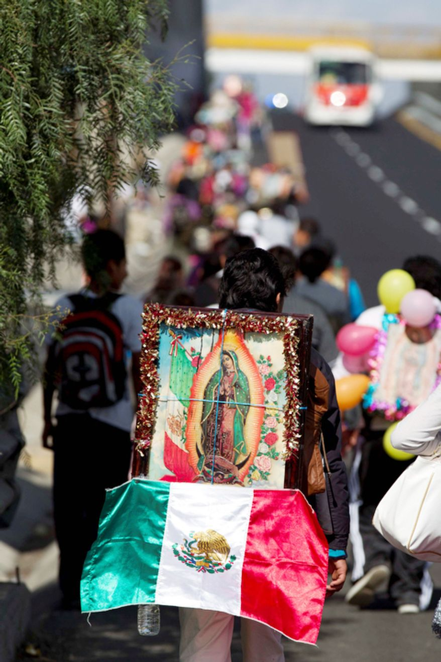 A pilgrim carries a statue of the Virgin of Guadalupe on his back as he makes his way with other pilgrims toward the Basilica of Guadalupe along a highway entering Mexico City. (AP Photo/Eduardo Verdugo)